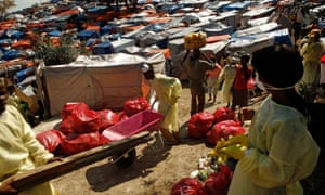 Local people were paid by Oxfam to remove trash and human waste at a camp outside Port-au-Prince after the earthquake in Haiti in 2010.