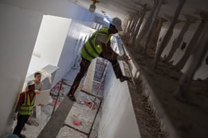 Contractors install ceiling panels at a hospital under construction in Ataq