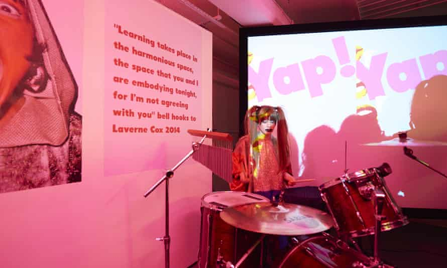 Gaggle drummer Sara Leigh Shaw performs under pink lighting in front of a projected backdrop and a quote from feminist bell hooks, as part of fig-2 week 9/50.