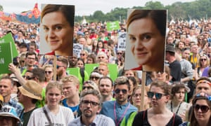 People hold posters of Jo Cox at a Glastonbury memorial in 2016