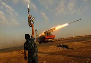 A rebel fighter celebrates as his comrades fire a rocket barrage toward the positions of troops loyal to the Libyan ruler, Muammar Gaddafi, west of Ajdabiyah, Libya on 14 April 2011.