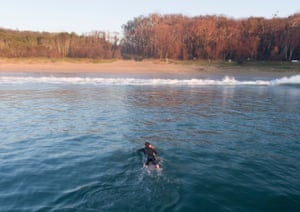 Surfer Nick Hopkins paddles on his surfboard in the water at McKenzies beach