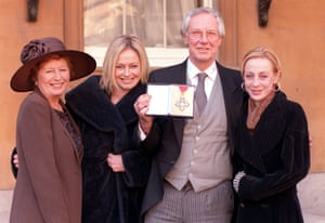 Norman holding up his CBE with wife Diana (far left) and daughters Samantha (left) and Emma (right) at the investiture ceremony at Buckingham Palace in 1998