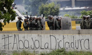The Spanish message 'Down with the dictatorship' covers a highway wall where security forces block an opposition march from reaching the National Electoral Council headquarters in Caracas.