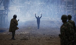 FILE - In this Thursday, Aug. 10, 2017 file photo A man seeking safety walks with his hands in the air through a thick cloud of tear gas towards riot police, as they clash with protesters throwing rocks in the Kawangware slum of Nairobi, Kenya on 10 August