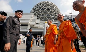 Police officers are met by monks at the Dhammakaya temple