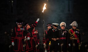 Beefeaters light the first torches in the installation.