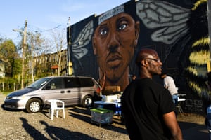 A Sandtown man stands by local artist Nether's mural of activist Kwame Rose, who confronted a CNN reporter on live TV