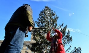Tourists take pictures near the controversial Christmas tree.