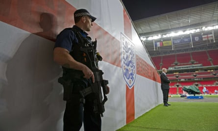 An armed police officer stands guard in the tunnel at Wembley stadium