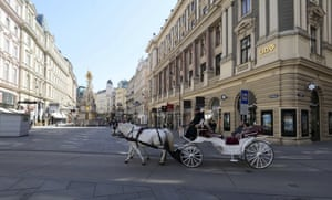 A fiaker, one of Vienna's famous horse-drawn carriages, drives through the empty pedestrian zone in Vienna