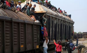 Ixtepec, Mexico. Central American migrants climb onto a train known as The Beast to continue their journey towards the United States
