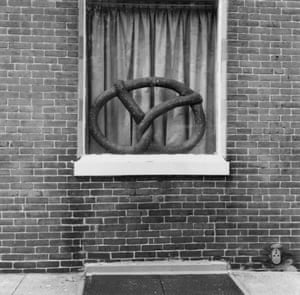 Pretzel Window, 1973. This photo by Will Brown depicts a pretzel too oversized to pass as food, mysteriously sitting in the narrow stage-like space between the window's pane and curtain