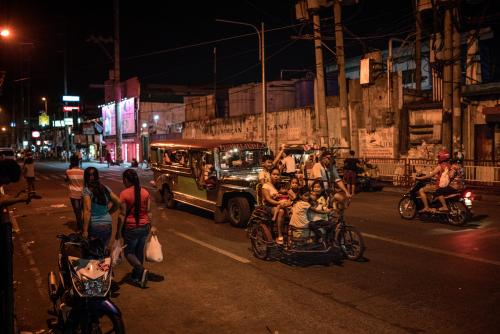 A pedi-trishaw filled to the brim with children on the main road outside of the Navotas slum, where Jasmine Durana lives.