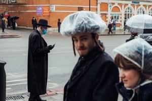 A man wearing a protective mask and gloves checks his phone in Stamford Hill