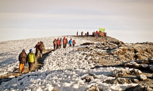 A group approaches the snowy summit of Kilimanjaro.
