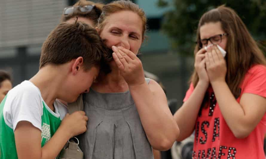 People mourn near the scene outside the OEZ shopping centre.