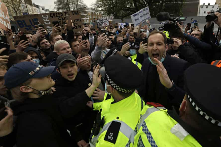 Former Chelsea goalkeeper Petr Cech, at right, behind a line of policemen, tries to calm down fans protesting outside Stamford Bridge