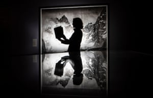A gallery assistant is reflected in a display cabinet