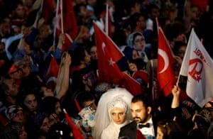 A bride and a groom attend a ceremony marking the first anniversary of the attempted coup in front of the Turkish Parliament in Ankara, Turkey