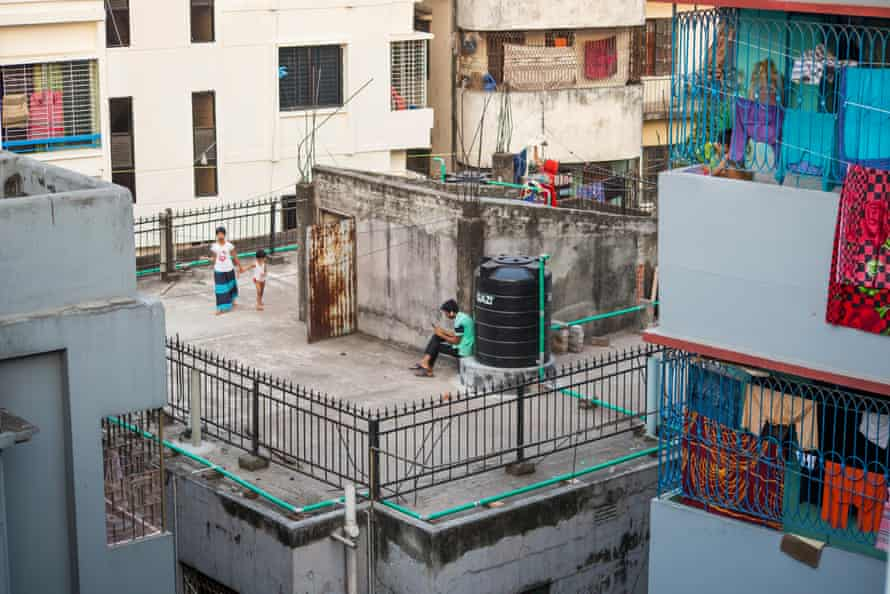 Several young people pass time on a city-block rooftop.