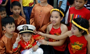 A child wears a US navy hat during a visit by sailors to Da Nang SOS Children's Village