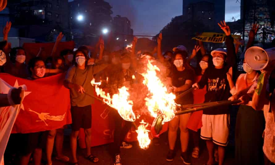 Protesters burn Myanmar flags during a demonstration against the military coup in Yangon on 29 July.