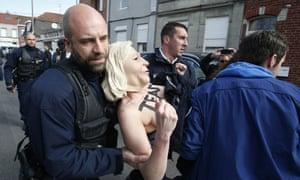 Police detain a Femen activist wearing a Marine Le Pen mask.