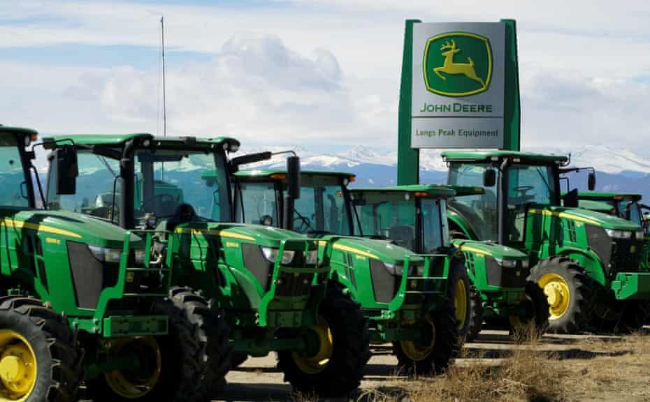 A row of green John Deere tractors on a dealer lot.