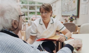 Female occupational therapist talking and listening to elderly man in a wheelchair; making an assessment on progress