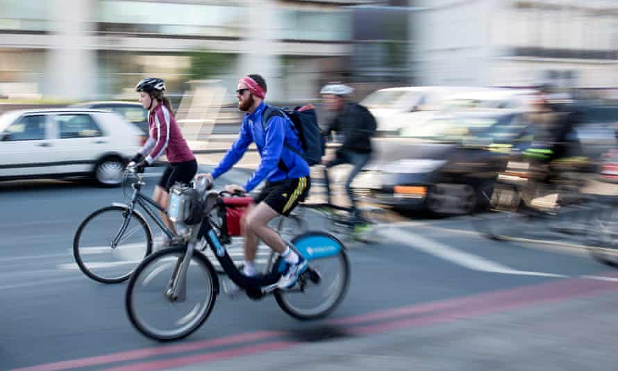 Two cyclists riding side-by-side on road