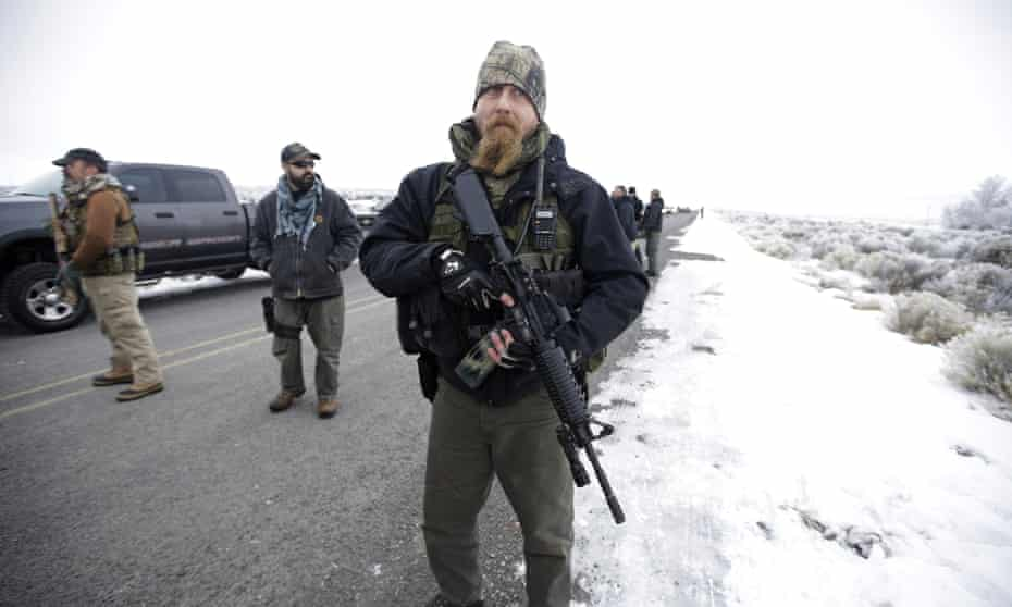 A man stands guard after members of the extremist 3% of Idaho group and several organizations arrive at the Malheur National Wildlife Refuge in 2016 during the standoff.