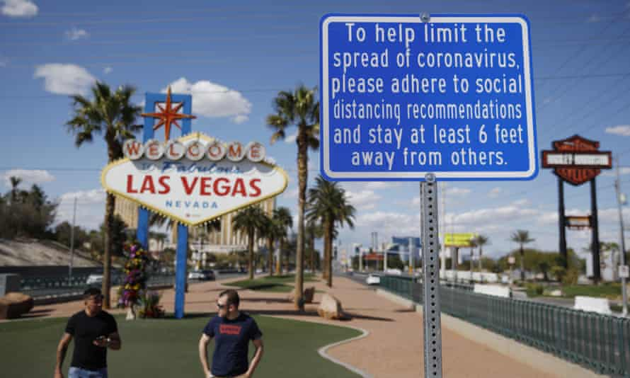 """a sign advises people to practice social distancing to slow the spread of the coronavirus at the """"Welcome to Fabulous Las Vegas Nevada"""" sign"""