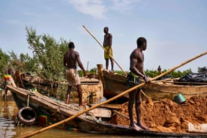 Diggers stand on their boats loaded with sand at an extraction site on the Niger River