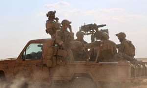 Armed men in uniform identified by Syrian Democratic forces as US special operations forces ride in the back of a pickup truck.