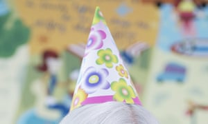 Top of elderly woman's hat with party hat perched on top