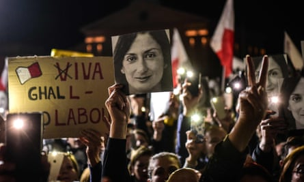 People holding placards and photographs of killed journalist Daphne Caruana Galizia outside the prime minister's office in Valletta.