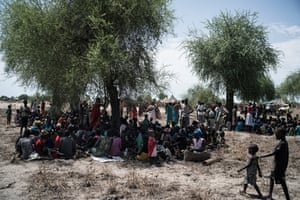In Bong, 10km from the frontline, people who have been driven from their homes by seek shelter from the sun under a tree