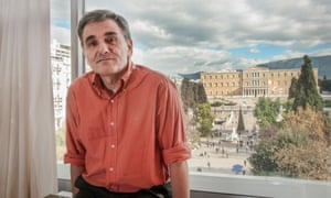 Euclid Tsakalotos standing at a window with a view of the Greek parliament building