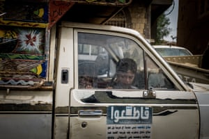 Children sit in a vehicle outside al-Jumhori hospital