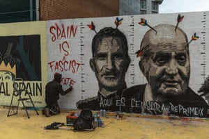A graffiti artist works on a mural supporting Pablo Hasél