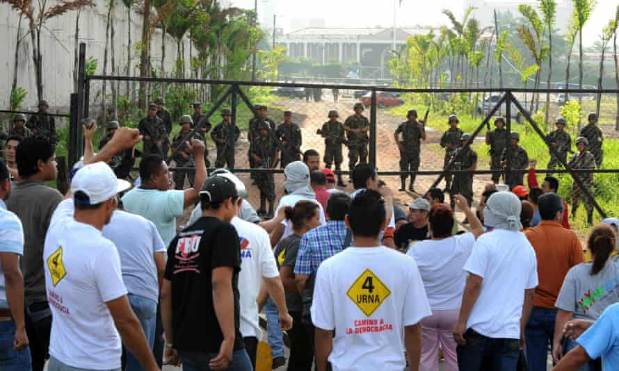 Angry Honduran civilians face troops near the presidential house in Tegucigalpa on 28 June 2009.