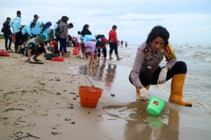 Police officers and residents use small buckets to remove globules of crude oil from the beach