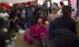 Rubi Ibarra looks at her mother Anaelda as journalists crowd around during a Mass part of Rubi's 15th birthday party.