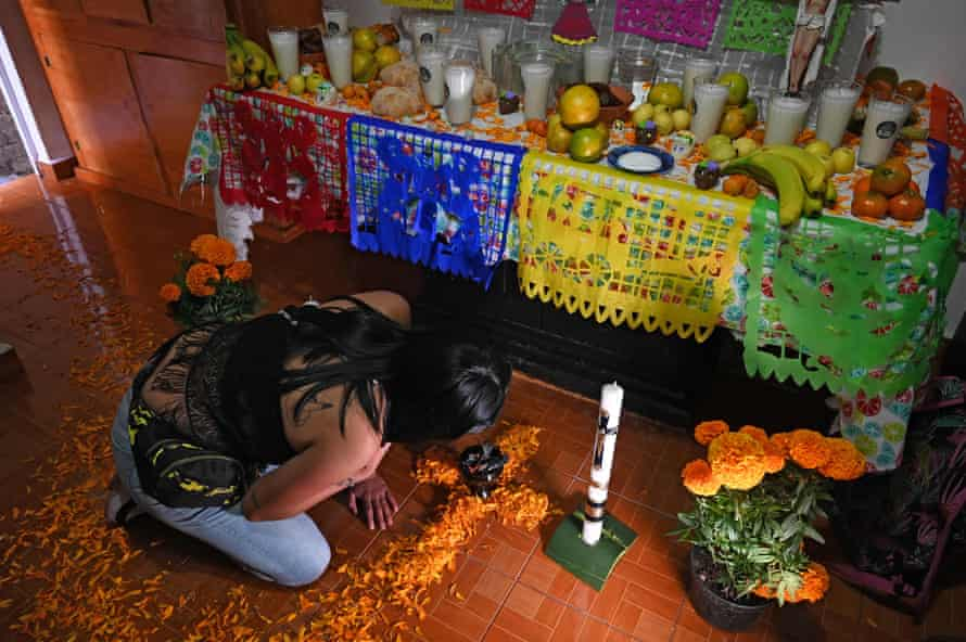A relative of Alma Delia Romero Sánchez, who died from Covid-19, prepares an altar in her honour for the Day of the Dead in Mexico City.
