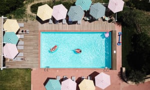 A rectangular swimming pool with multi-coloured patterned umbrellas, seen from above