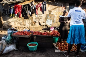 Two women exchange a few words while buying and selling tomatoes on a Kibera evening