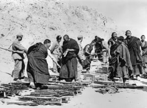 Monks in Tibet, surrounded by People's Liberation Army forces, lay down their arms in 1959 after an unsuccessful uprising against Chinese rule.
