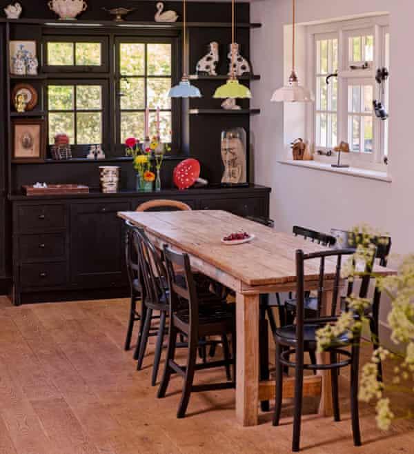 Black shelving in the kitchen of the home of fashion designers Justin Thornton and Thea Bregazzi in Walberswick, Suffolk