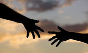 Two people reaching for each other.